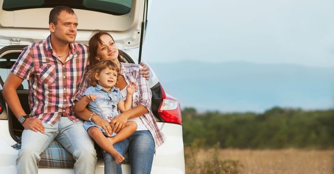Family sitting on tailgate of car